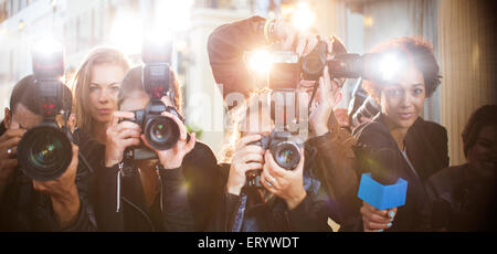 Portrait of paparazzi in a row with cameras and microphone - Stock Photo