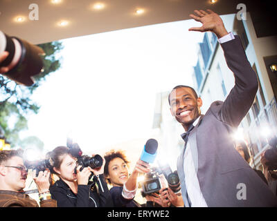 Waving celebrity being interviewed and photographed by paparazzi at event - Stock Photo