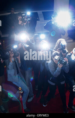 Paparazzi photographers pointing cameras at red carpet event - Stock Photo