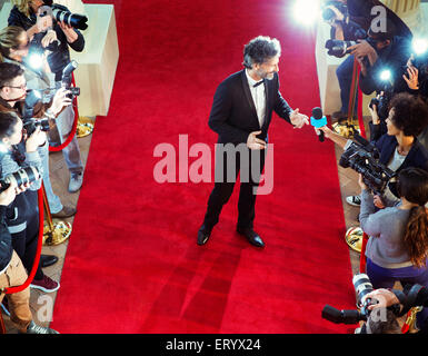 Celebrity on red carpet being interviewed and photographed by paparazzi - Stock Photo