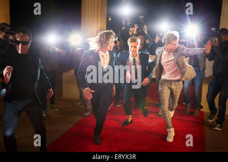 Enthusiastic celebrities arriving and running from paparazzi at red carpet event - Stock Photo