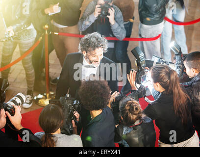 Celebrity being interviewed and photographed by paparazzi photographers at red carpet event - Stock Photo