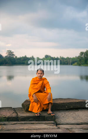 SIEM REAP, CAMBODIA - OCTOBER 30, 2014: Novice Buddhist monk in orange robe sits along the moat near the entrance - Stock Photo