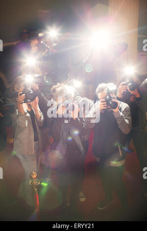 Lens flare flash from paparazzi photographers cameras - Stock Photo