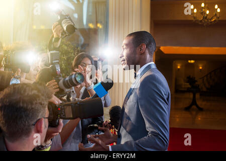 Celebrity being interviewed and photographed by paparazzi at red carpet event - Stock Photo