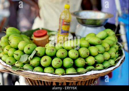 The green mangoes to overcome summer heat in the Sunday Market in Kolkata India - Stock Photo