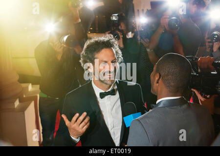 Celebrity being interviewed and photographed by paparazzi photographers at event - Stock Photo