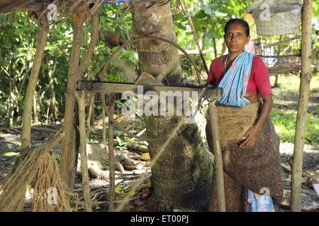 Keralite woman making coir rope in cottage ; traditional method ; Kerala ; India NO MR - Stock Photo