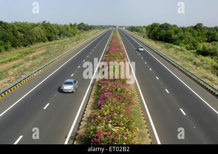 Ahmedabad Vadodara Expressway with flowers bed National Highways Authority of India Gujarat India - Stock Photo