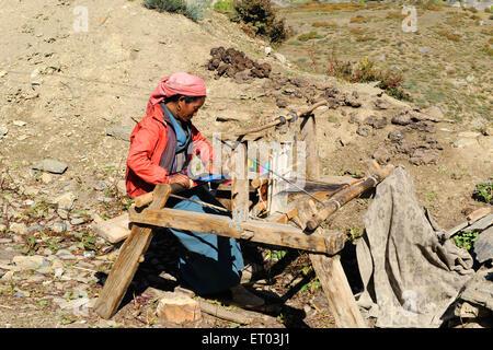Woman weaving woollen on handloom ; Muktinath ; Nepal NO MR - Stock Photo