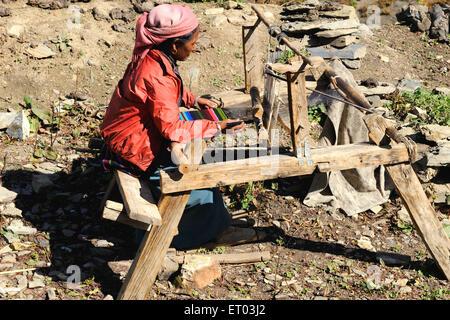 Woman weaving woollen on handloom ; Muktinath ; Nepal - Stock Photo