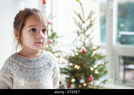Wide-eyed girl looking up in front of Christmas tree - Stock Photo