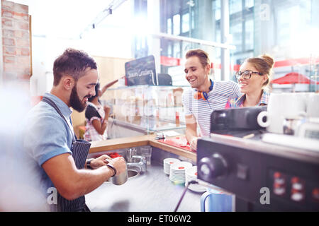 Customers watching barista make coffee in cafe - Stock Photo