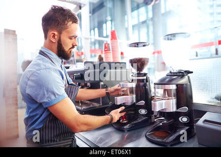 Barista making coffee in cafe - Stock Photo