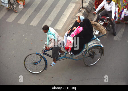 Two women riding on tricycle rickshaw pulled by rickshaw driver in Ranchi city capital of Jharkhand ; India - Stock Photo