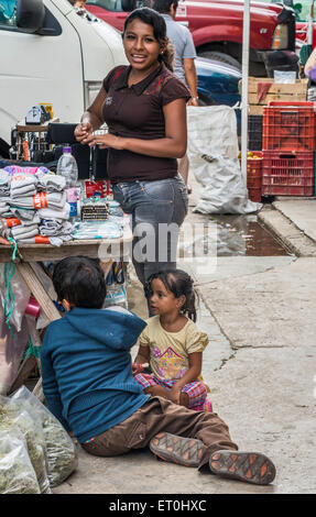 Young woman, children at market stall on Calle 22, street in Ciudad del Carmen, Campeche state, Mexico - Stock Photo