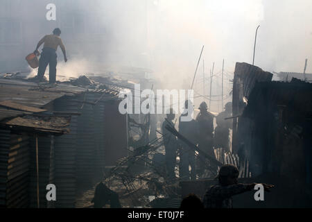 Residents along firemen trying to douse off the fire which broke mhada colony situated at Versova ; Andheri ; Mumbai - Stock Photo