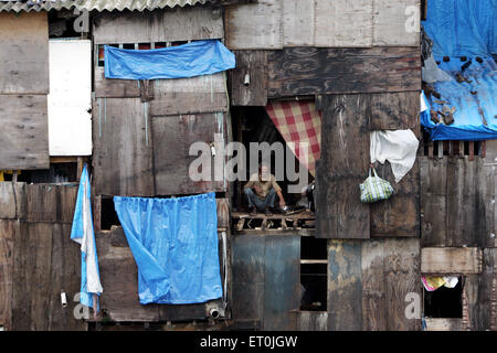 An old man can be seen sitting at a door Behrampada slum in Bandra Bombay Mumbai Maharashtra India - Stock Photo