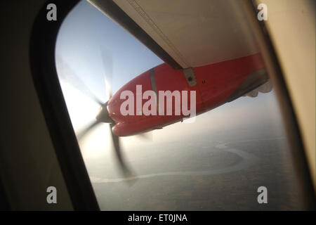 Wing of aircraft in the sky can be seen through the window ; India - Stock Photo