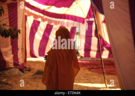 Sikh woman devotee with her head covered standing in tent near Sachkhand Saheb Gurudwara in Nanded ; Maharashtra - Stock Photo