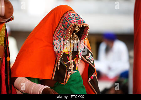 Nomad woman dressed in their traditional colourful attire sitting outside the Sachkhand Saheb Gurudwara in Nanded - Stock Photo
