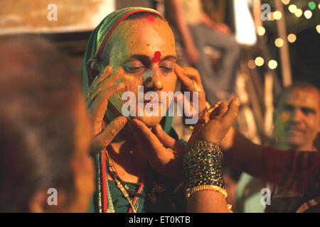 Haldi or turmeric being smeared on face of eunuch ; wedding of eunuchs on occasion of Bewa Purnima at Ghatkopar - Stock Photo