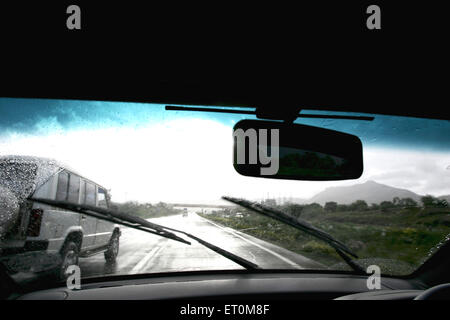 Car wipers wiping front glass on the Expressway between Mumbai Pune  ; Maharashtra ; India - Stock Photo