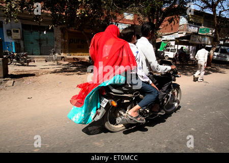 Three member family riding on two wheeler motor cycle in city of Ahmedabad ; Gujarat ; India - Stock Photo