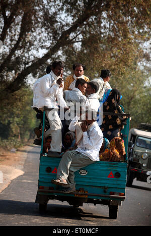 Group of people travelling sitting behind three wheeler scooter seen on highway towards Ahmedabad ; Gujarat ; India - Stock Photo