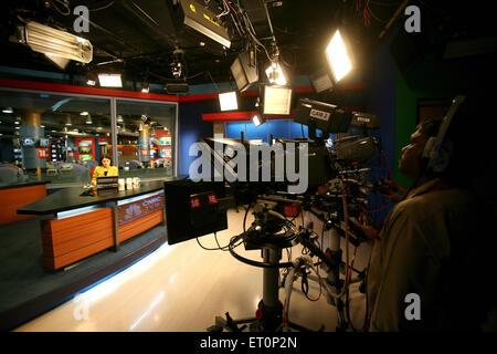 Cameraman shooting anchor with news in newsroom of cnbc channel ; Bombay Mumbai ; Maharashtra ; India - Stock Photo