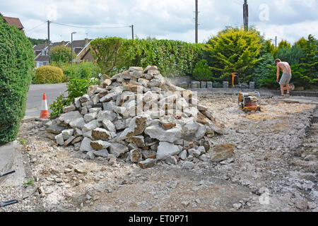 Front garden of residential property having concrete driveway broken up ready for new block paving - Stock Photo