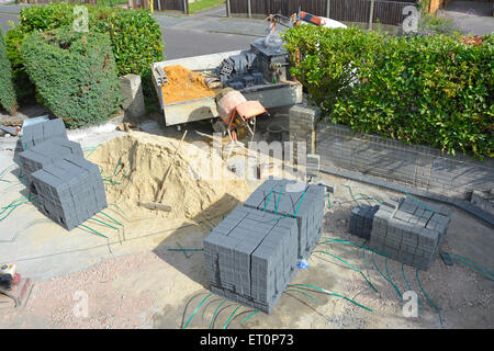 Sand and paving blocks in front garden of residential property creating a new car driveway after removal of old - Stock Photo