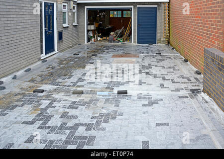 Plastic sheeting laid over new concrete block paving to stop storm downpours reaching sand sub base before completion - Stock Photo