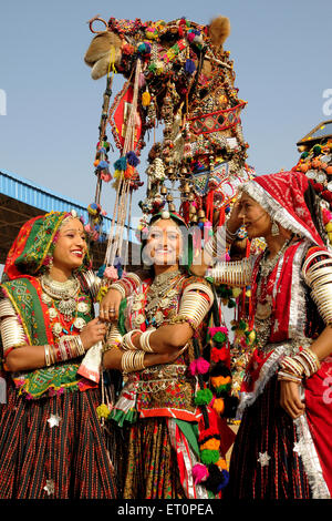 Girls in traditional jewellery and rajasthani costume standing in front of decorated camel in Pushkar fair ; Rajasthan - Stock Photo