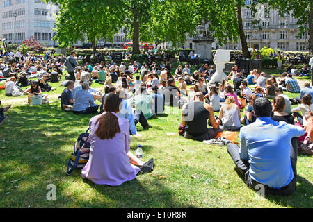 London people in Cavendish Square gardens mainly office and shop workers sitting on grass at lunch time break on - Stock Photo