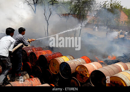Firemen trying to douse off fire while scrap warehouse ; Jodhpur ; Rajasthan ; India - Stock Photo