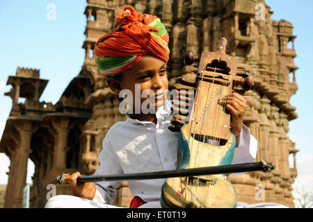 Boy playing sarangi ; Deval ; Mandore ; Jodhpur ; Rajasthan ; India MR#769L - Stock Photo
