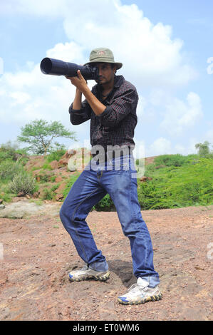 Photographer giving pose while photo shoot ; India Mr#786 - Stock Photo