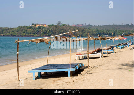 Wooden beds on sand at keri beach in pernem Canacona Goa India - nmk 177250 - Stock Photo