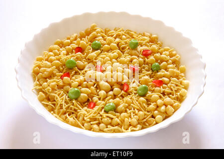 Snacks ; boondi bhel namkeen savoury garnish with green peas and pomegranate in round bowl on white background - Stock Photo