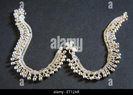Silver anklets pair on black background - Stock Photo