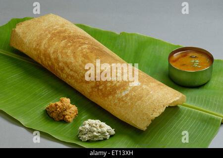 South Indian food Dosa on green banana leaf with coconut chutney and sambhar India - Stock Photo