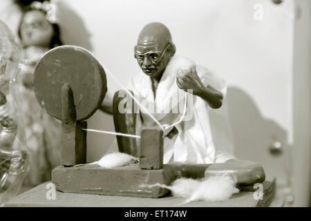 Statue of Mahatma Gandhi working on Charkha Maharashtra India Asia - Stock Photo