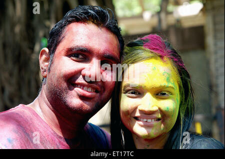 Indian couple faces smeared with color powder celebrating Holi Festival of colours India MR#364 - Stock Photo