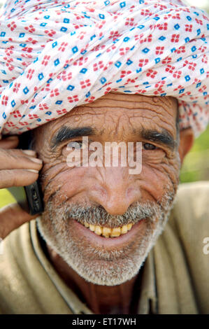 Old Man Talking on Mobile Phone rajasthani India Asia - Stock Photo