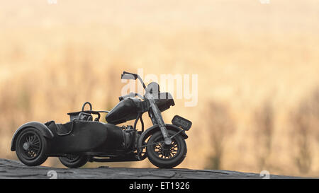 Close-up of miniature toy motorcycle on natural background - Stock Photo