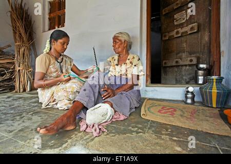 Health worker of NGO Chinmaya Organization of Rural Development CORD checking blood pressure mercury patient doorstep - Stock Photo