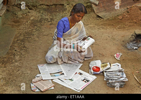 Volunteer of NGO Chinmaya Organization of Rural Development CORD making recycled paper bags - Stock Photo