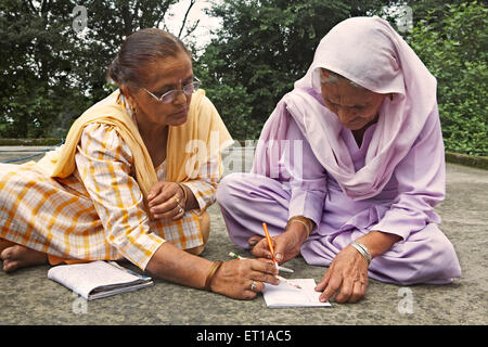 Volunteer teaching old lady to write adult literacy program socio economic initiative started by NGO Chinmaya Organization - Stock Photo