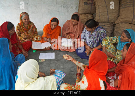 Women volunteers of NGO Chinmaya Organization of Rural Development CORD collecting contribution from members - Stock Photo